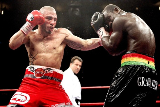A bloodied Cotto digs a left hook to a covering Clottey (photo by Chris Farina - Top Rank, Copyright 2009)