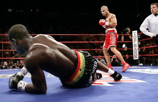 Cotto stands over Clottey in the first round as referee Arthur Mercante, Jr. looks on (photo by Chris Farina - Top Rank, copyright 2009)