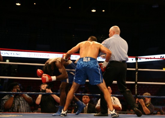 Referee Celestino Ruiz stops the battery as Reynolds cringes from the onslaught.