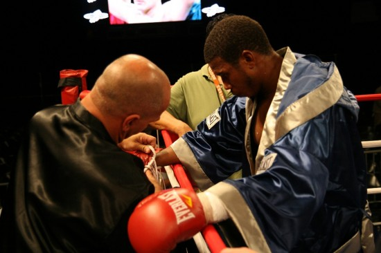 A dejected Chris Gray has his gloves removed by a cornerman.