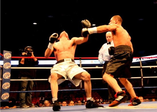 Referee Celestino Ruiz looks on as Russell Fiore (right) devastates Jose Hernandez with a smashing left hook to the chin