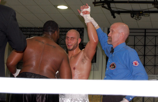 Referee John O'Brien raises Latoria's hand as Glover congratulates him