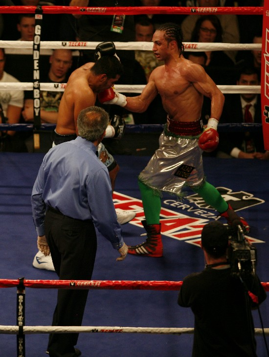 M(right) unloads an uppercut on the chin of Diaz as referee Genaro Rodriguez looks on
