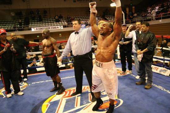 Referee Kurt Spivey raises the fist of a victorious Derrick Findley.