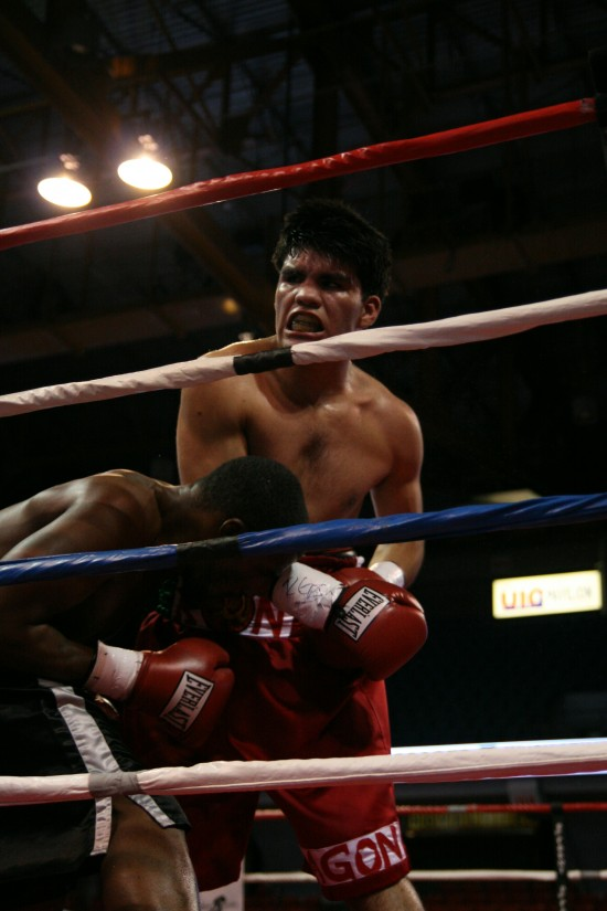 Ramon Valenzuela (right) grimaces as he attacks Chris Grays on the ropes.