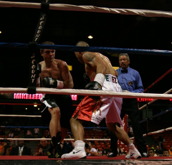 Novikov (left) and Perez trade along the ropes as referee Gerald Scott looks on.