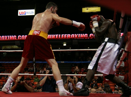 Lee (at left) drives Walker back to the ropes with a sharp right jab.
