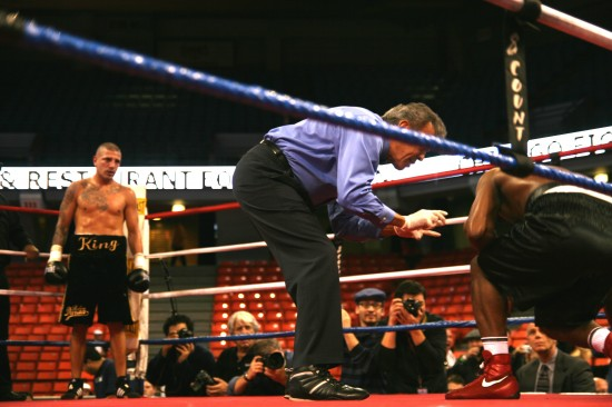 Referee Genaro Rodriguez administers a count to Gonzalez as Estrada looks on.