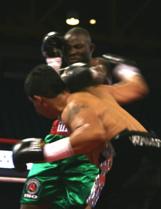 Hernandez (foreground) fires a looping right hook as Adama tries his best to fend him off.