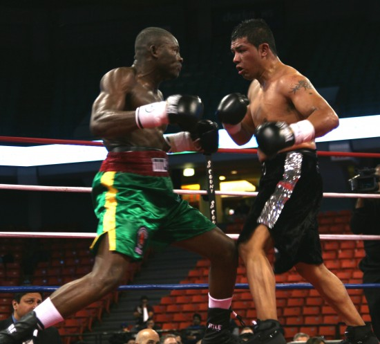 Adama (left) fires a looping right as he and Hernandez mix it up in a thrilling bout.