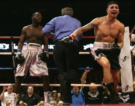 Donovan George celebrates his win as referee Genaro Rodriguez intervenes.