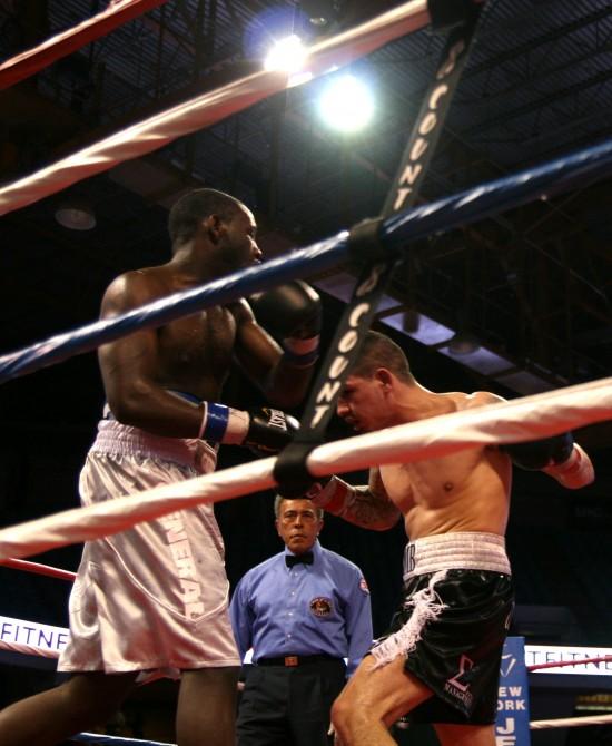 Taylor (left) and George slug along the ropes as referee Genaro Rodriguez looks on.