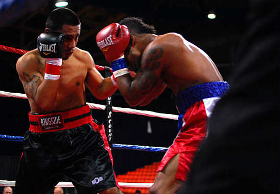 Juan Bustamante (L) and Jose Rivera trade punches inside