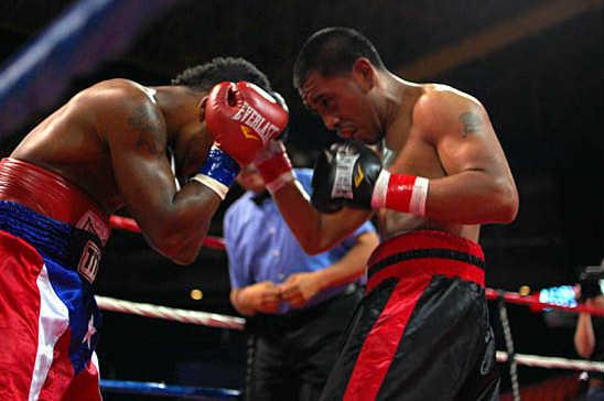 Bustamante (R) sneaks in an uppercut through Rivera's guard