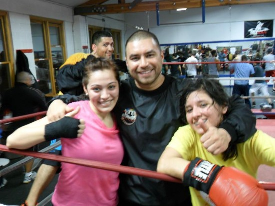 Chicago Boxing Club's Rick Ramos poses with a couple female boxers.