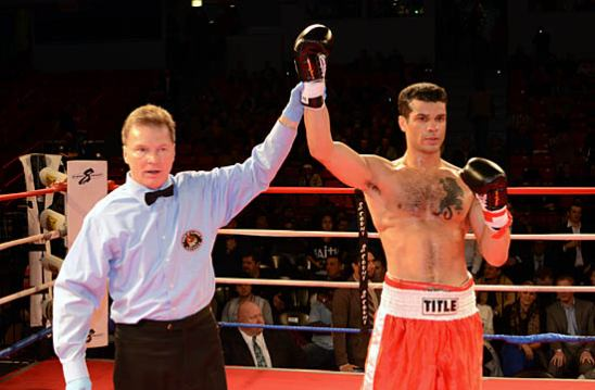 Referee Pete Podgorski (L) makes Paul Littleton's TKO win in his pro debut official