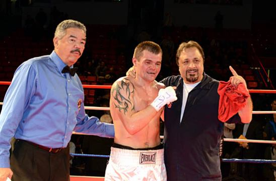 Polyakov (C) celebrates his victory with Referee Gerald Scott (L) and trainer Sam Colonna