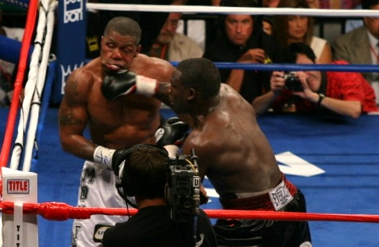 Hassim Rahman (right) seen here landing a crushing right to Monte Barret's chin in winning the Interim WBC Heavyweight title in 2005 (photo by Tom Glunz)