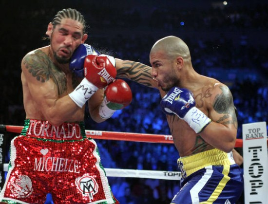 Miguel Cotto (right) bounces a right off the chin of Antonio Margarito in their rematch.  (Photo Credit : Chris Farina - Top Rank, copyright 2011)