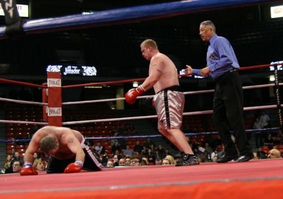 Tate flattens his man as referee Gerald Scott observes.