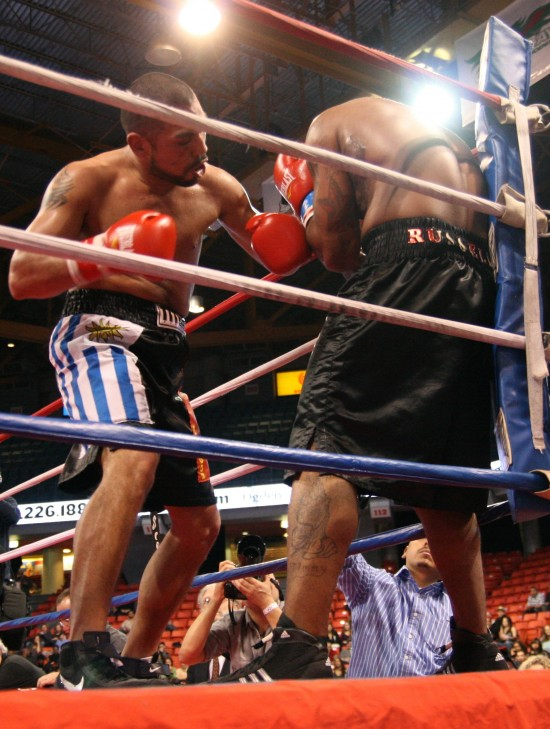 Ortuz batters Russell in a corner moments before the stoppage.