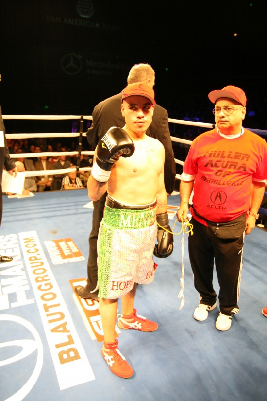 A victorious Mendez raises his right fist as trainer George Hernandez looks on.
