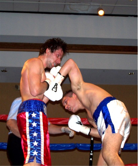 Welby (right) connects with a potent left to Holmes' chin (photo by Juan C. Ayllon)