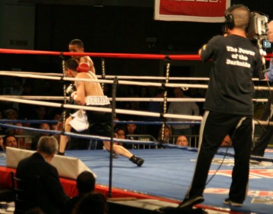 Oritz (foreground) punishes Santos on the ropes.
