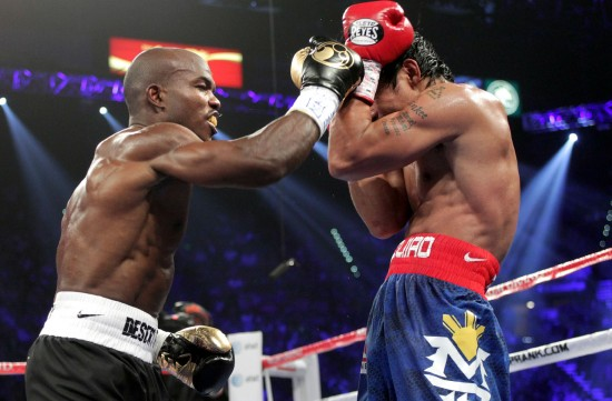 Timothy Bradley (left) fires a right as Manny Pacquiao covers (photo by Chris Farina, Top Rank, copyright 2012)
