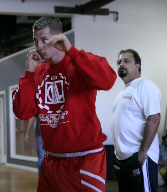 Andrzej Fonfara shadow boxes in the mirror at left, as his trainer, Sam Colonna, looks on (photo by Juan C. Ayllon)