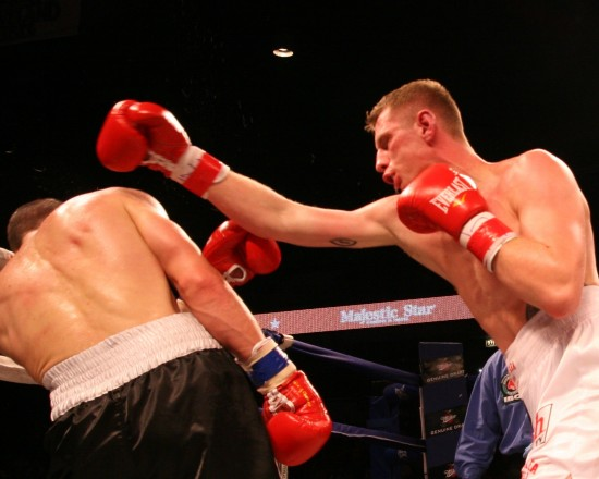 Fonfara (right) batters Karpency in the first round of his championship-winning effort (photo by Belle Ayllon)