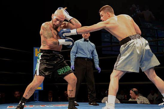 Jonathan Manos (R) sneaks in a jab on Bill Finn in the opening round of his pro debut