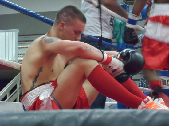 A dejected Anthony Linenfelser sits on the canvas in his loss to Sharpe.