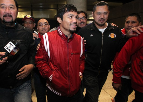 Manny Pacquiao, at center in red, arrives in Los Angeles (photo by Chris Farina - Top Rank, Copyright 2014)