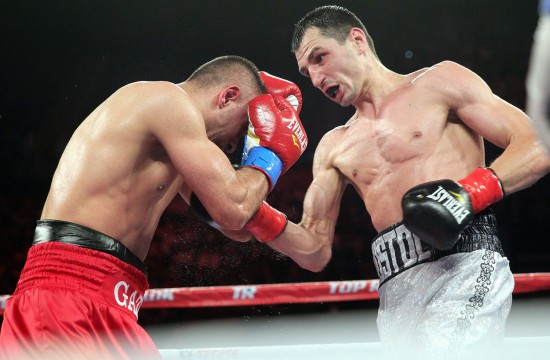 Postal Drills Aydin with a punishing uppercut en route to stopping him (photo by Chris Farina - Top Rank, Copyright 2014)