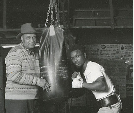Parker working the heavy bag, under the watchful eye of trainer Willie Reddish.